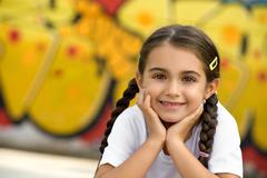 Smiling Cute Little Girl with Hands on Face Stock Photos