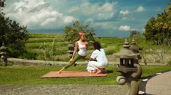 Balinese yoga instructor teaching woman to stand in warrior pose Stock Footage