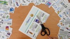 Top shot of man cutting coupon with various coupons background Stock Footage