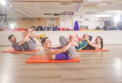 Three people happy smiling fitness mat happy abs core exercise Stock Photos