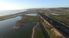 High aerial over the California coastline, train and highway near San Diego. Stock Footage