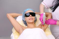Having underarm laser hair removal epilation Stock Photos