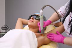 Having underarm laser hair removal epilation Stock Photos