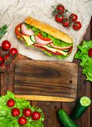 Cooking lunch, sandwich with meat and vegetables on wooden table Stock Photos