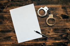 Police handcuffs and blank paper on investigator detective's wor Stock Photos