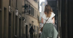Girl in street in Italy on cell phone, pauses to look around Stock Footage