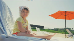 Happy little baby girl take sunbath in chair at beach Stock Footage