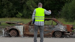 Inspector take pictures of burned down car wreck on the side of the road Stock Footage