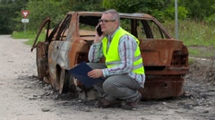 Inspector talking on smart phone near burned down car wreck Stock Footage