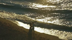 Elvoved pair kiss on sunset evening seashore. Couple kisses as waves breaking on Stock Footage