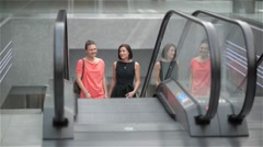 Two girls moving upstairs on escalator in shopping mall, friends are shopping in - stock footage