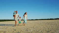 Steadicam shot: Cheerful family running across the sand. Parents and two young Stock Footage