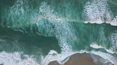 An aerial perspective looking straight down at the ocean with waves rolling in. Stock Footage