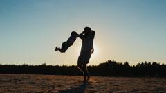 Healthy father playing with his son at sunset - circling it. Beautiful round Stock Footage