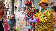 People in clown suit and makeup inflates balloons and makes shape form character Stock Footage