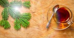 Glass Cup of tea on an old rustic table with pine branch.New year. Stock Photos