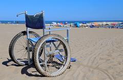 Aluminum wheelchair on the sand and many umbrellas on the beach Stock Photos