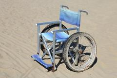 Isolated wheelchair made of aluminum with special wheels on thesand Stock Photos