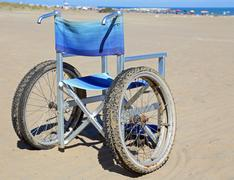 Modern aluminum wheelchairs with double tires moving on beach Stock Photos