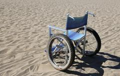 Isolated wheelchair with special wheels on beach sand Stock Photos