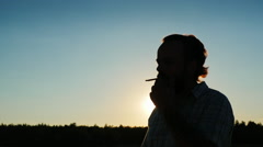 Silhouette of a bearded man who smokes at sunset Stock Footage