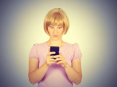 Closeup portrait anxious  young woman looking at phone seeing bad news. Stock Photos