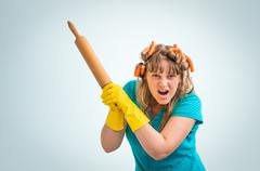 Mad and crazy housewife woman with kitchen roller isolated on blue background Stock Photos