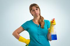 Tired housewife woman in yellow gloves with a rag and detergent on blue backg Stock Photos