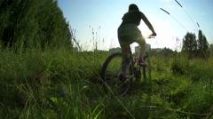 Teen girl riding a bike through green grass field in city park, hot summer day Stock Footage