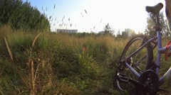 Girl going forward to camera with bicycle in tall grass in city park Stock Footage