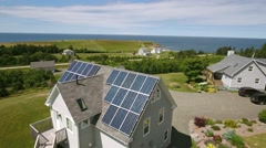 Aerial shot of solar panels on roof of house on ocean coast Stock Footage