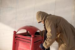 Homeless looking for food in the garbage bin Stock Photos