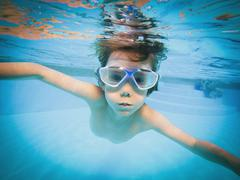 Portrait of boy swimming underwater in swimming pool Stock Photos