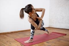 Young beautiful athletic girl practicing indoor yoga asanas. Parsvakonasana Stock Photos