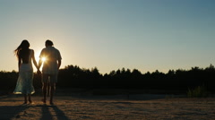 Steadicam shot: Silhouette of a young couple, which goes towards the setting sun - stock footage