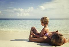 Mother and son laying and relaxing on tropical beach Stock Photos