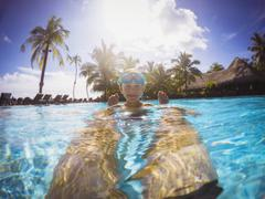 Portrait smiling boy in sunny tropical swimming pool Stock Photos