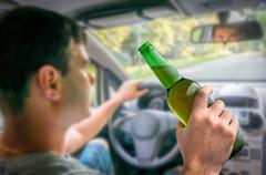Young unfocused man drinking beer and driving car Kuvituskuvat