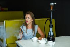 Beautiful woman smoking a hookah and drinking tea in a cafe Stock Photos