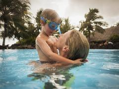 Mother and son hugging in swimming pool Stock Photos
