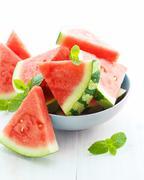 Triangular slices of fresh watermelon on white wooden background Stock Photos