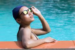 Girl in bikini and swimming cap leaning on the edge of the pool Stock Photos