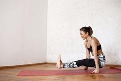 Young beautiful athletic girl practicing indoor yoga arm-balance handstand asana Stock Photos