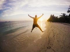 Portrait of exuberant man jumping on tropical beach at sunset Stock Photos