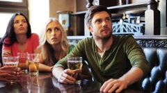 Friends with beer watching football at bar or pub Stock Footage