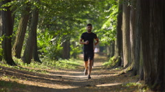 The sportsman run in the beatiful forest. Super telephoto lens shot Stock Footage