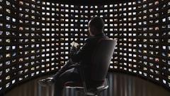 Man watching video on monitors - stock photo