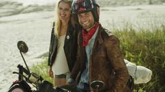 Portrait smiling young couple at motorcycle on beach Stock Photos