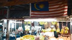 Malasian Flag hangs over produce on jalan alor food street Stock Footage