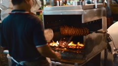 Meat is cooked over open flame on jalan alor food street Stock Footage